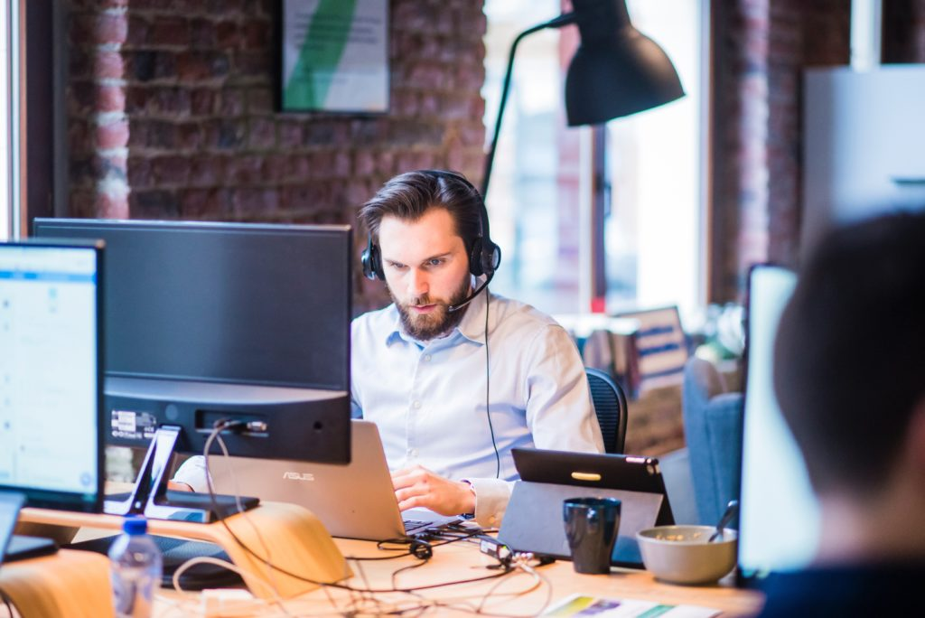man on headset at desk looking at computer