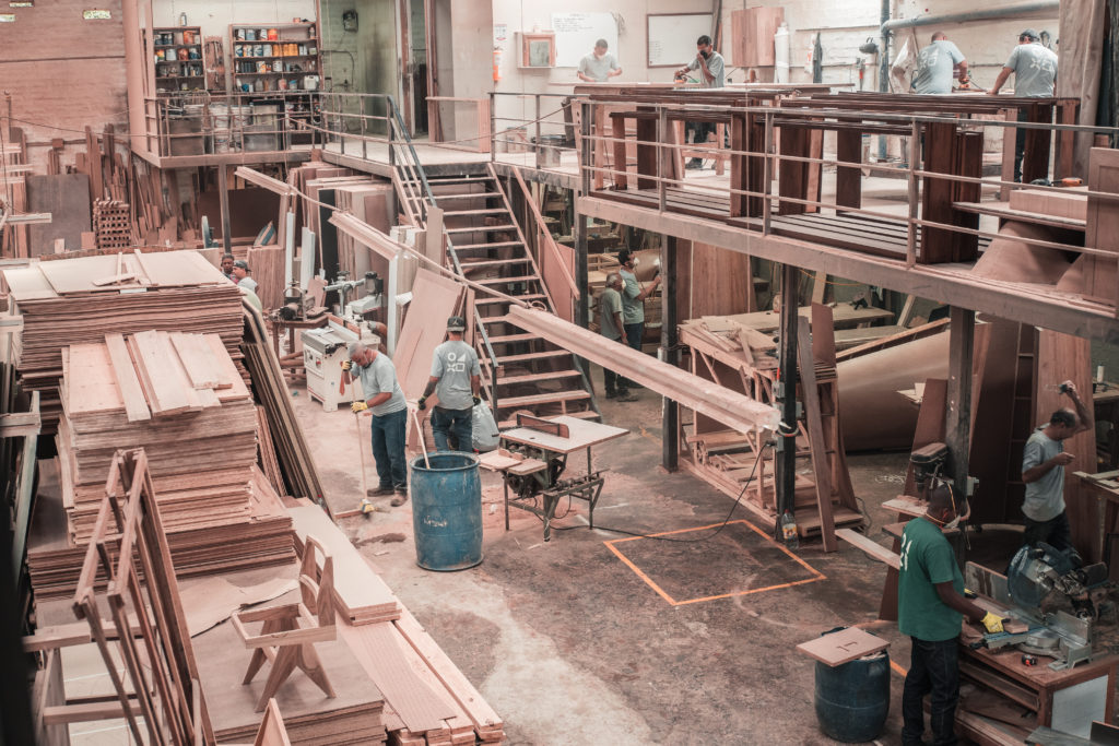 people working with lumber on a manufacturing floor
