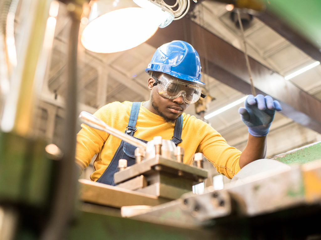 Serious busy young factory engineer in hardhat and safety goggles examining milling lathe and repairing it while working at production plant