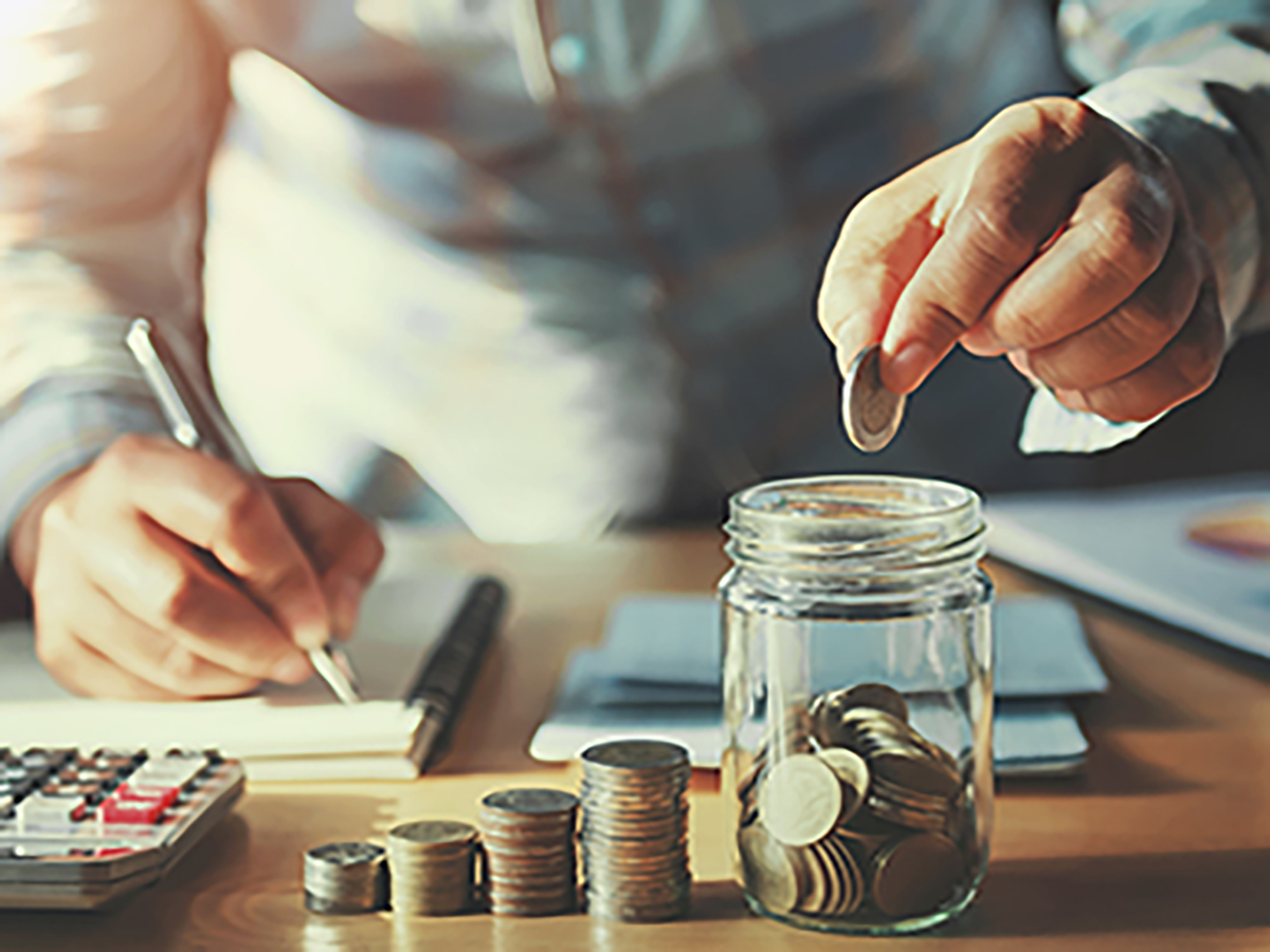 businessman saving money concept. hand holding coins putting in