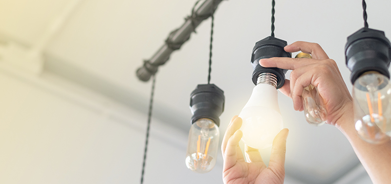LED light Power saving concept. Asia man changing compact-fluorescent (CFL) bulbs with new bulb.