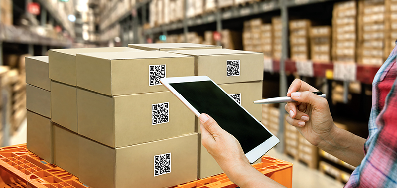 Augmented reality and smart logistic concept. Hand holding tablet with AR application for check order pick time around the world and supply chain in smart factory background.