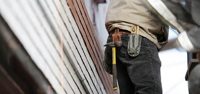 Man Wearing Black Denim Pants With Carrying Hammer on Holster