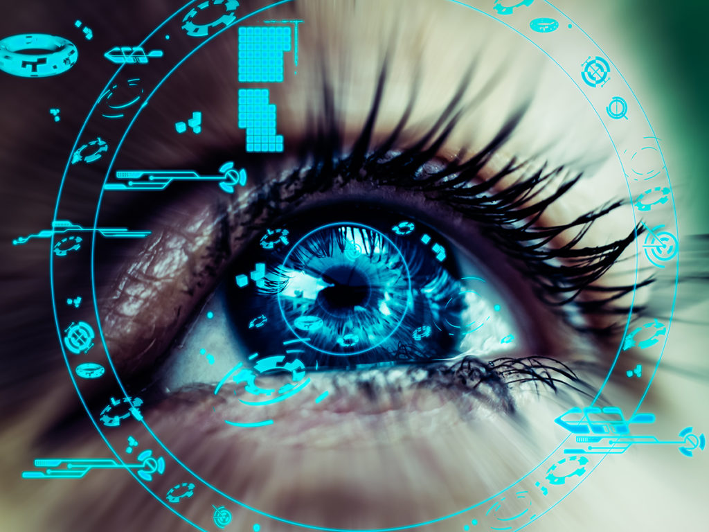 close up of blue eye surrounded by digital technology
