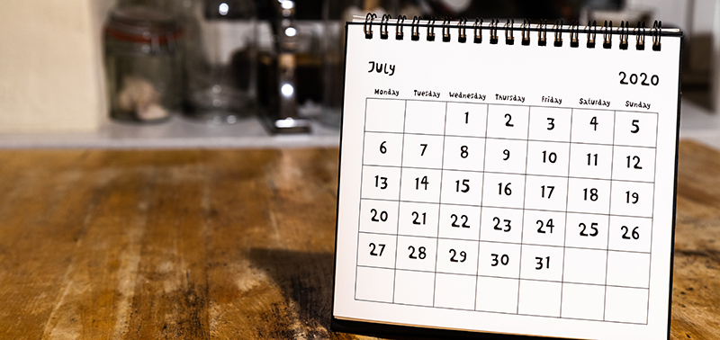 July 2020 calendar - month page on wooden table in the kitchen