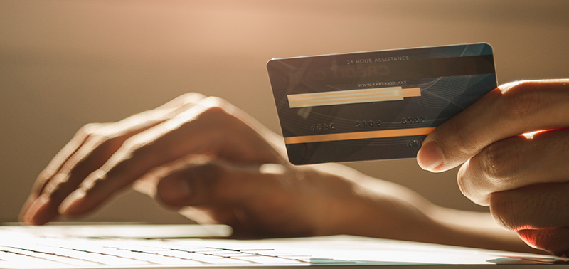 Hands using laptop computer and holding credit card at working desk for online shopping, E-commerce, Internet banking, Panoramic web banner with copy space.