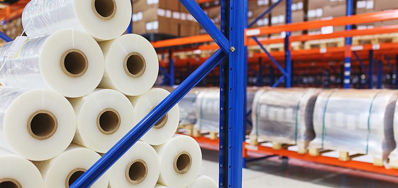 system of address storage of products, materials and goods in a warehouse. Rolls of polyethylene film in stock. Modern warehouse and storage systems.
