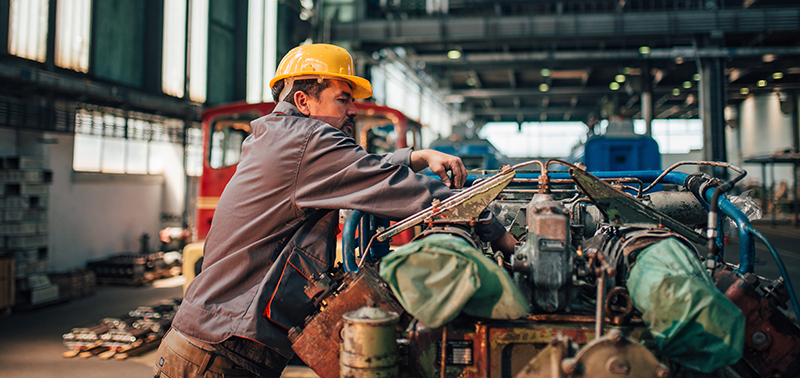 Train mechanic working on engine at heavy industry factory.