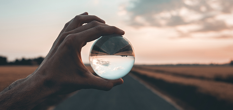 man holding crystal ball over a road at sunset