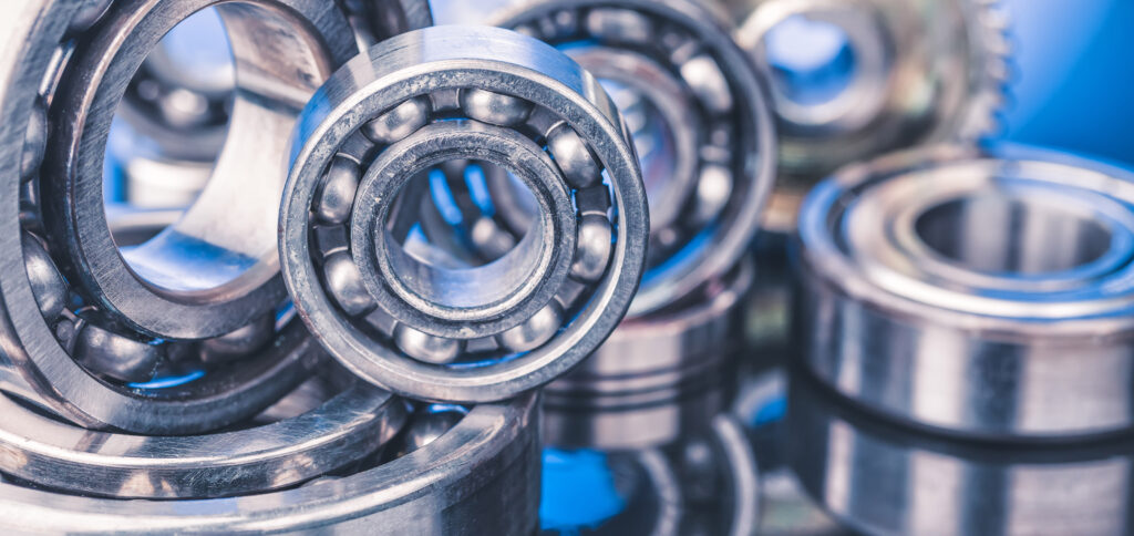 Group of various ball bearings close up on nice blue background with reflections.