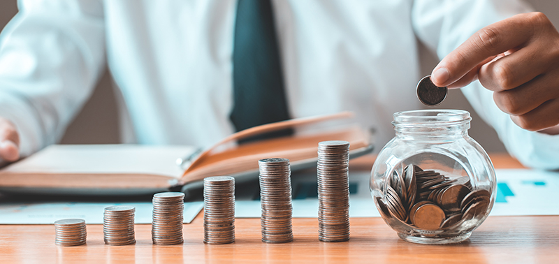 Financial businessman with coins put in a jar, Saving money for future growth and knowing how to manage your spending wisely, Saving money for business growth or long-term profitability.