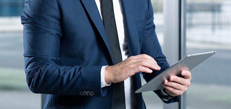 Businessman wearing suit and tie using his tablet