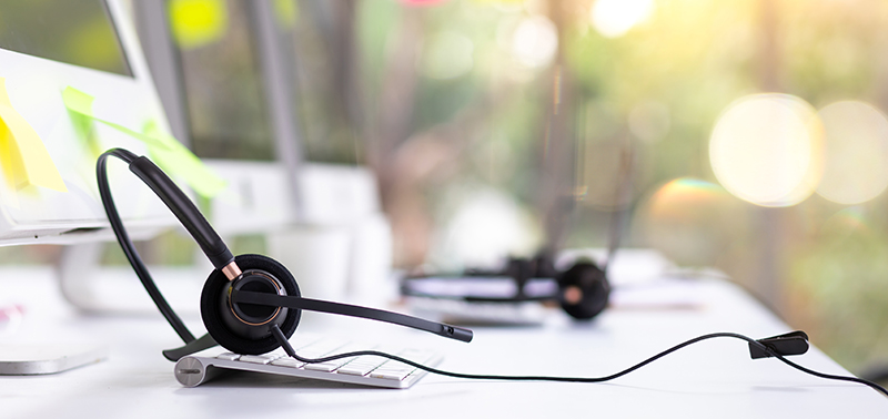 VOIP headset on desk with computer desktop at customer service and marketing support workplace. Office supplies of customer service. Communication support, call center and helpline concept.