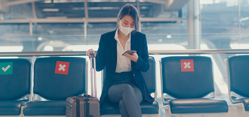 business lady traveller wear suit sitting with suitcase and use smart phone chat message in bench wait for flight at airport. Business travel commuter in covid pandemic, Business travel concept.