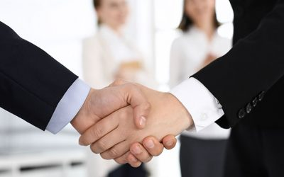 Businessman and woman shaking hands with colleagues at the background. Handshake at meeting in office. Concept of success in business.