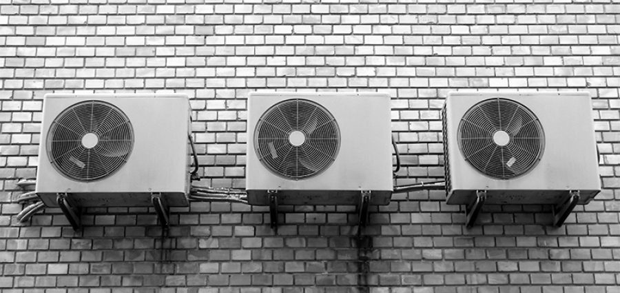 three air conditioning units on a white brick wall