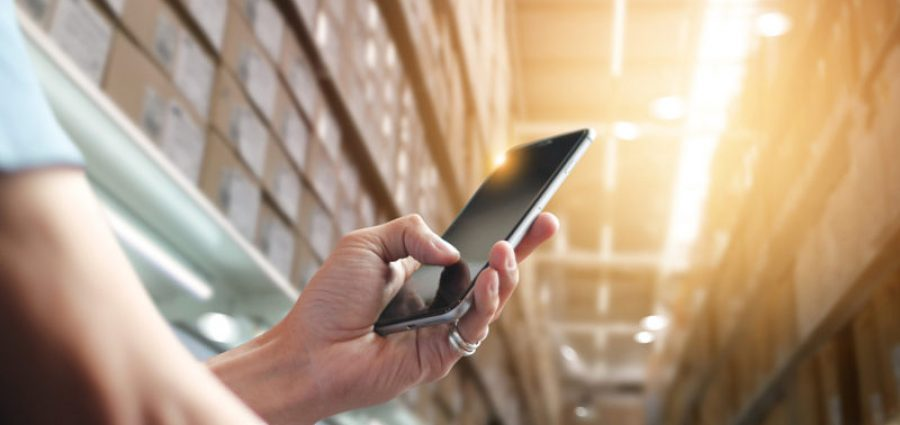Person in warehouse using cellphone to automate processes