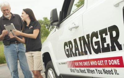 Grainger sales call man and woman outside van.