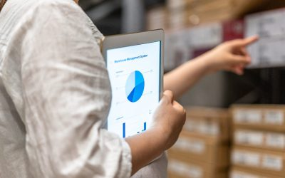 man holding tablet with pie chart in warehouse