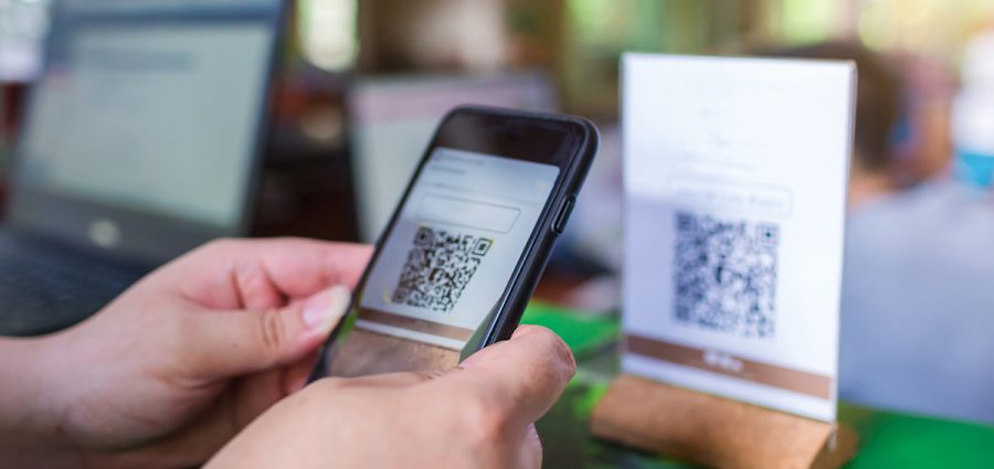 Closeup of a hand holding phone and scanning QR code with blurry