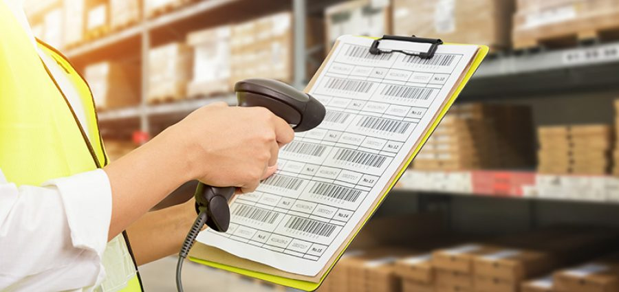 Worker checking and scanning package by laser barcode scanner in modern warehouse.