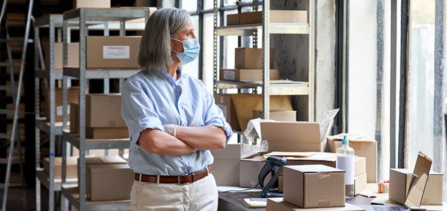 Older mature female online store small business owner, manager, stock worker, entrepreneur wearing face mask and gloves standing with arms crossed at workplace in warehouse looking through window.