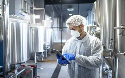 man in lab working with tablet and chemicals