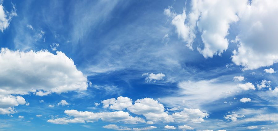 white fluffy clouds on blue sky in summer on sunny day. Beautiful cloudscape background