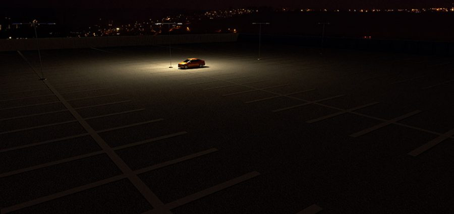 3D rendering of a sinngle car in a parking lot representing the concept of working late