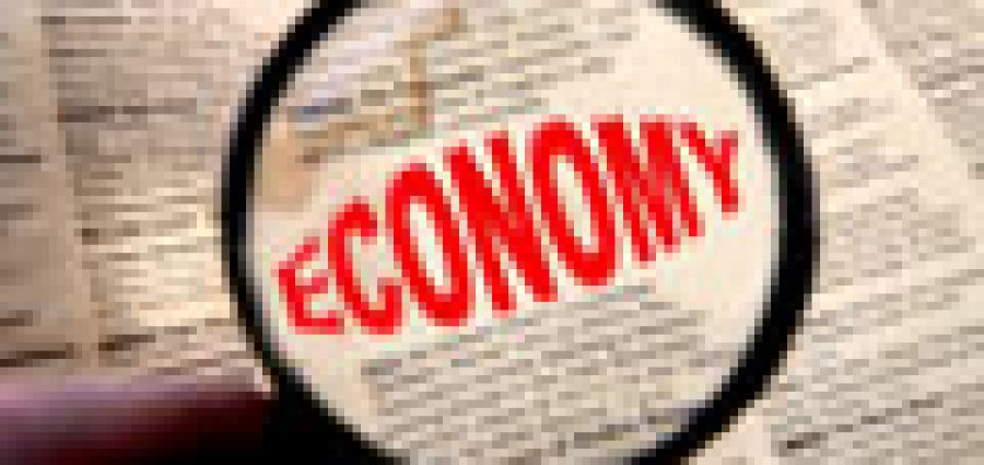 newspaper with the word economy in red enlarged through a magnifying glass.