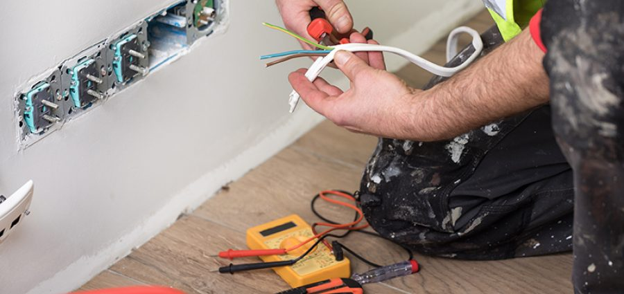 electrician separating wiring next to white wall