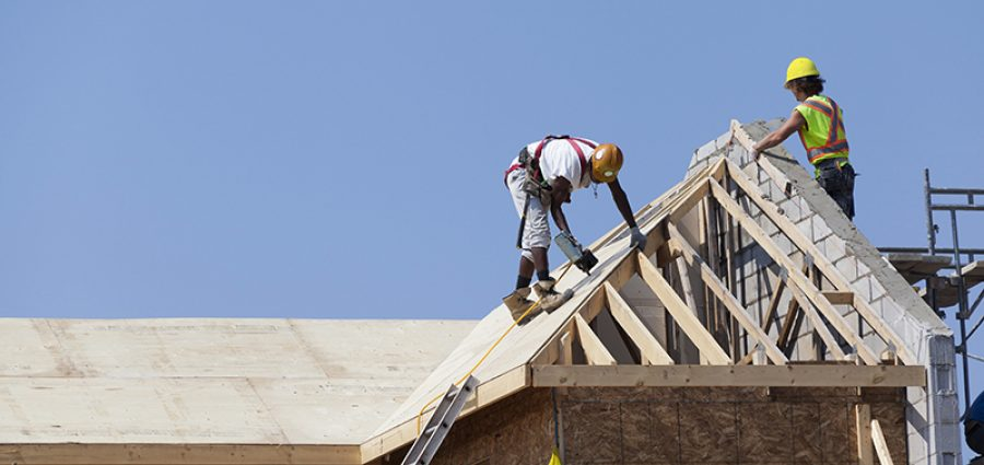 Workers are working on the roof at construction housing construction
