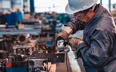 Skilled industrial worker grinding metal part.