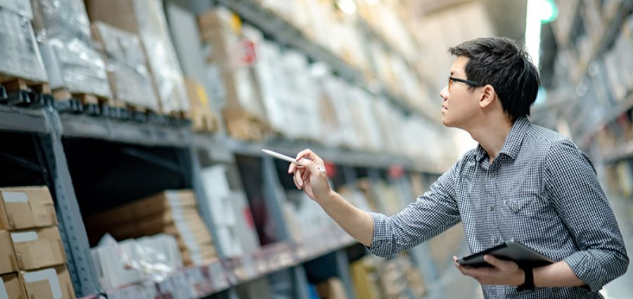 Young man worker doing stocktaking of product in cardboard box on shelves in warehouse by using digital tablet and pen. Physical inventory count concept