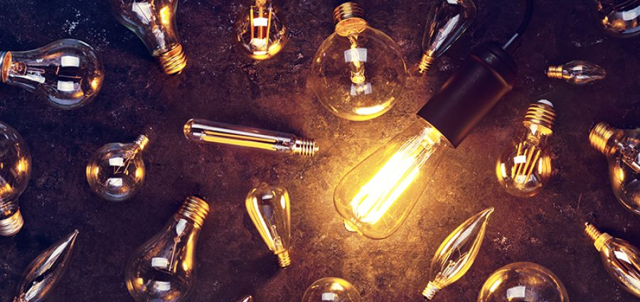 Vintage old light bulb glowing yellow on rough dark background surrounded by burnt out bulbs. Idea, creativity concept.