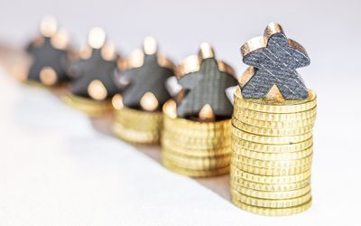 stacks of gold coins with people-shaped silver figures on top