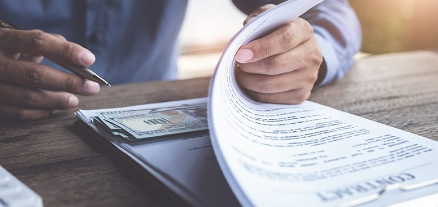 Compensation, fees, pay, bribery concept, Business man open contract document and look at dollar simulation money at under document. Contracting for financial gain.