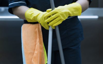 Latin woman between 20-35 years working as a cleaner in the office with cleaning implements