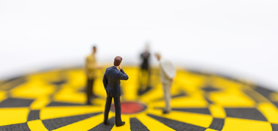 Business, Planning, Succession and Management Concept. Close up of group of businessman miniature figure standing and looking to center of yellow and black dart board on white background.