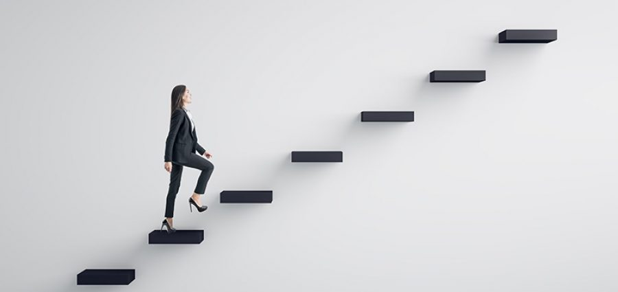Side view of young businesswoman climbing stairs to success on concrete wall background. Leadership and career development concept