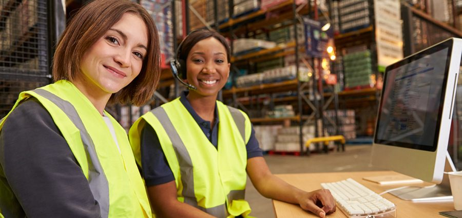 Two female colleagues in a warehouse office look to camera
