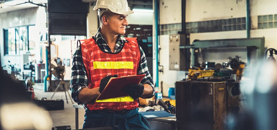 Manufacturing worker working with clipboard to do job procedure checklist . Factory production line occupation quality control concept .