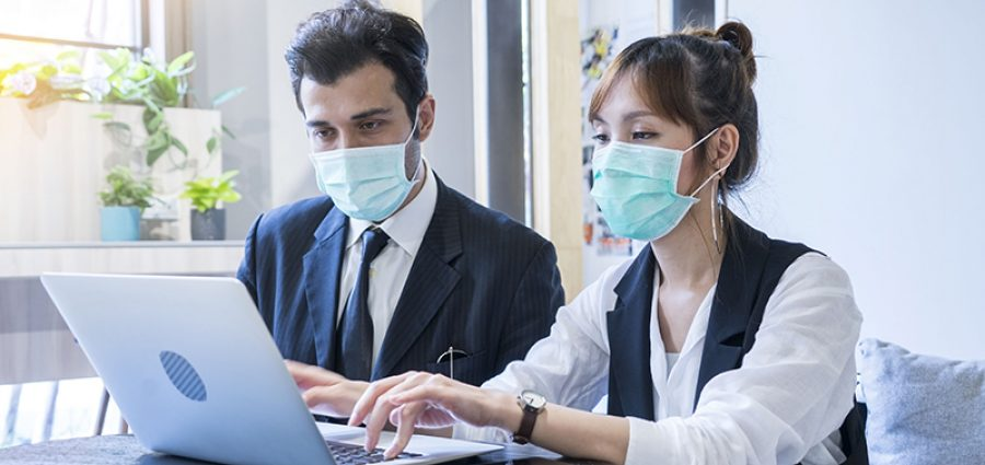man and woman wearing masks working on a laptop together