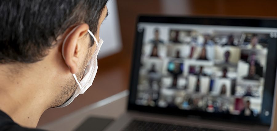 Man using a mask and having a video conference with work team am